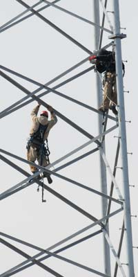 A tower worker free-climbs.