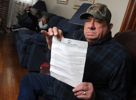 Hay holds a letter from the Commonwealth of Virginia informing him his unemployment benefits have been cut from $800 to $100 per month.